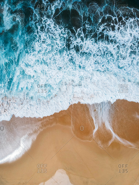 Aerial drone shot of deep blue waves crashing on sandy beach Mexico