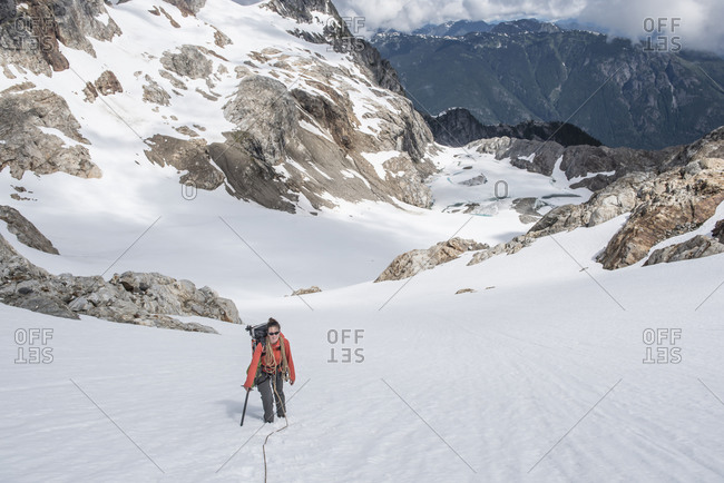 A woman climbs a glacier on Snowfield Peak in the North Cascades