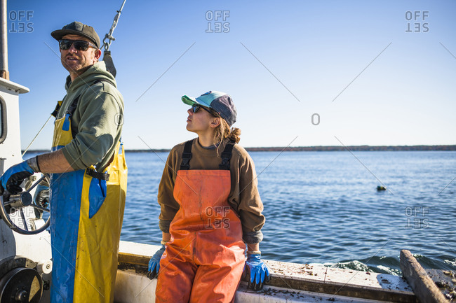 Woman and man working on shellfishing boat on Narragansett Bay