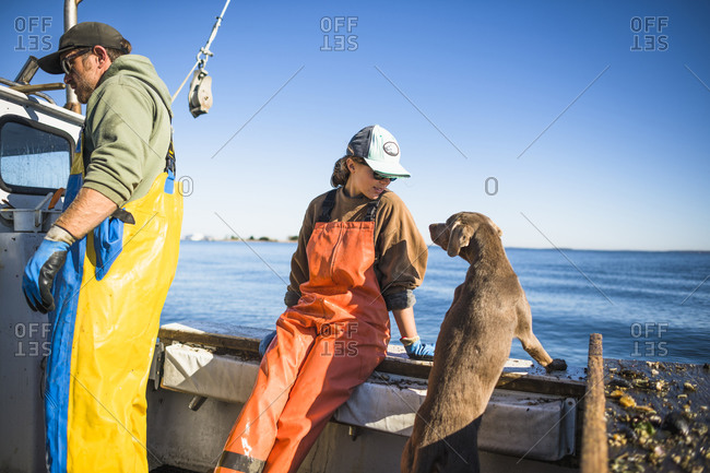 Woman and dog working on shellfishing boat on Narragansett Bay