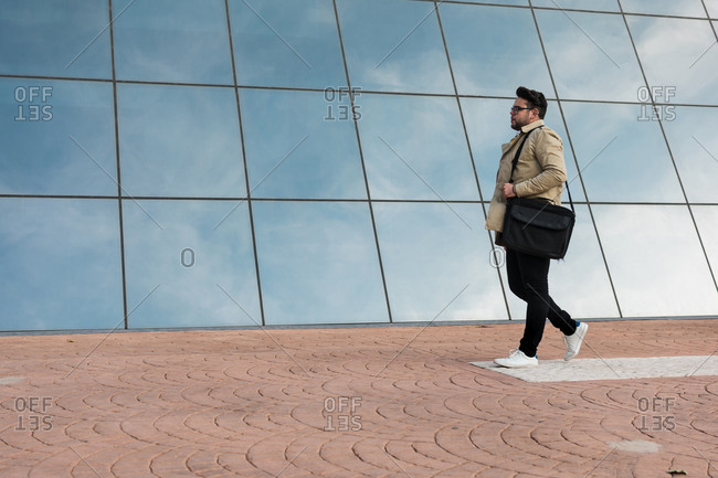 Businessman is walking with a glazed building in the back