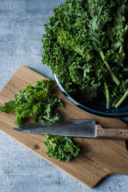 Top view of bowl of kale, cutting board with knife and chopped kale.