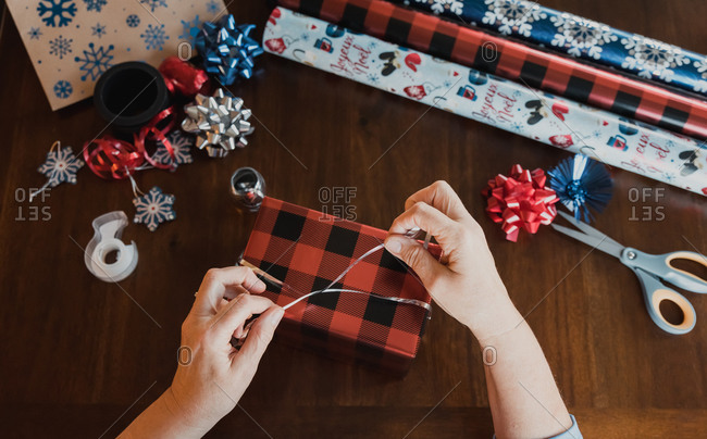 Hands wrapping present at wooden table with gift wrapping supplies.