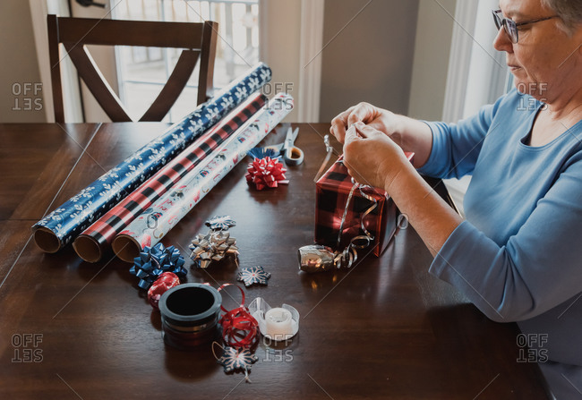 Mature woman wrapping a Christmas present at a wooden table.