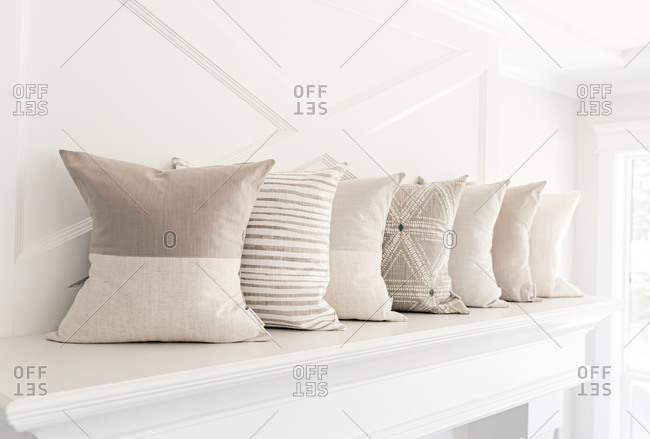 Neutral pillows on a fireplace mantle