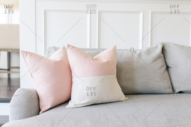 Pink pillows on a grey couch