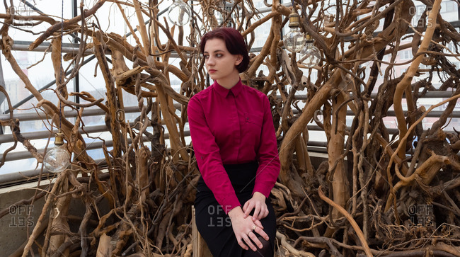 Girl in a red shirt and skirt against the background of trees