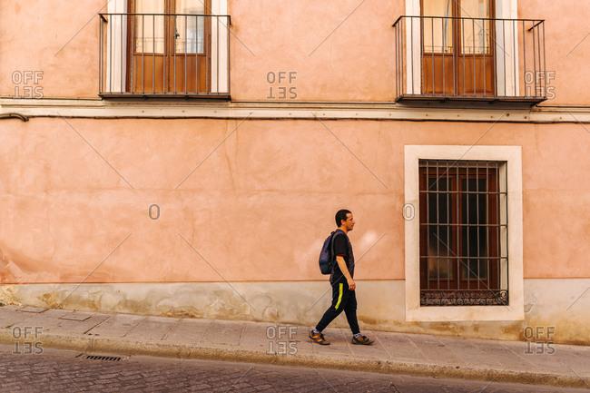 Man with sportswear walking along a picturesque street in Spain, Cuenca