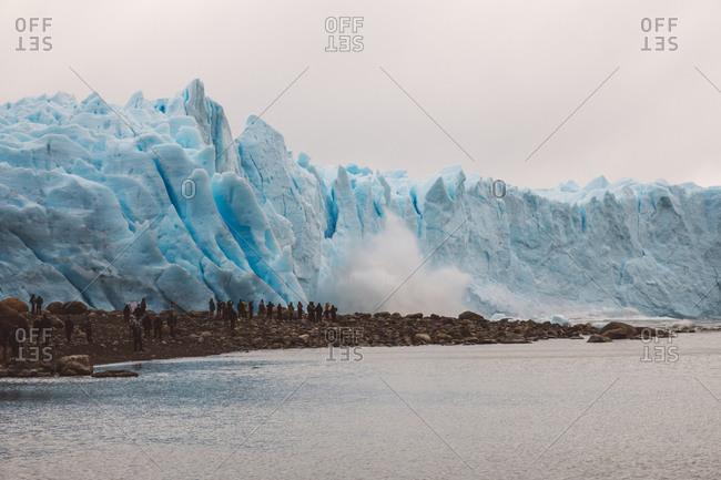 Crowd admiring geyser near glacier