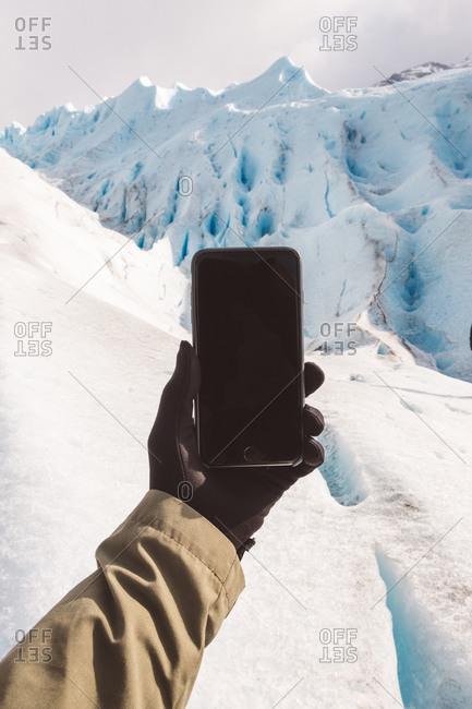 Crop traveler shooting glacier with smartphone