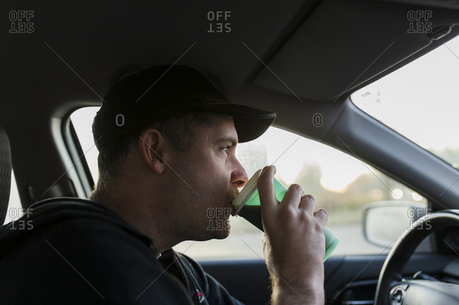 Male Industrial worker commuting to work drinking coffee while driving