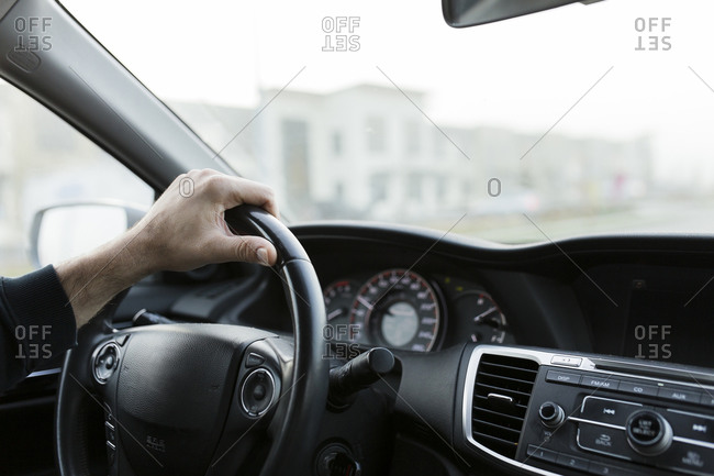 Male hand on black steering wheel driving a car commuting to work