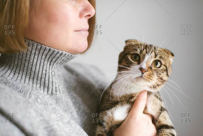 Woman holding beautiful cat on white background