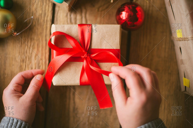 Woman wrapping Christmas gifts on wooden background