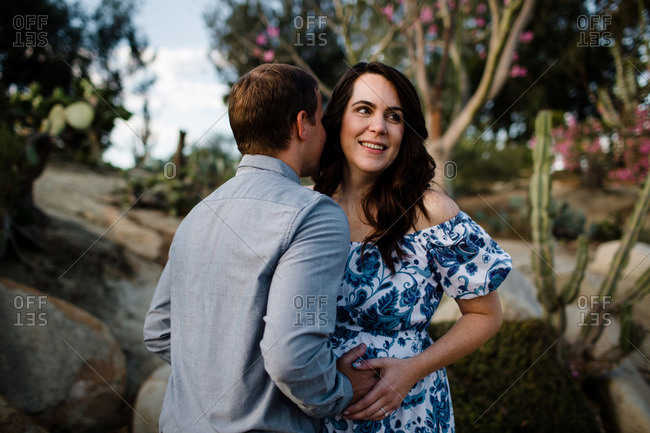 Husband Hugging Pregnant Wife as She Smiles