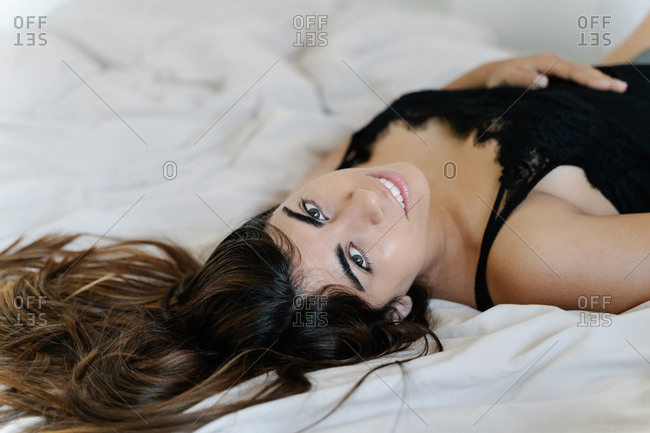 Beautiful young brunette in black dress lying on bed