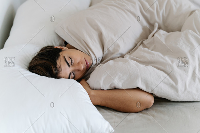 Side View Of A Young Beautiful Woman Sleeping In White Bed