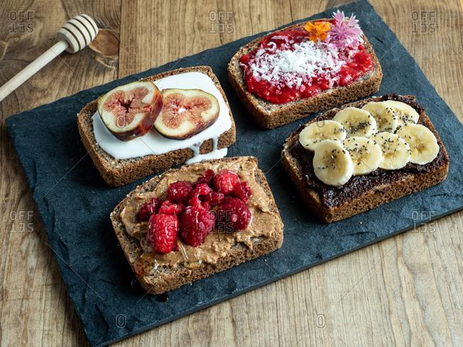 Toast including bananas, raspberries, figs, yogurt on slate platter