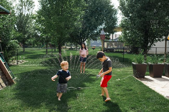 Siblings playing in backyard and running through sprinkler in summer