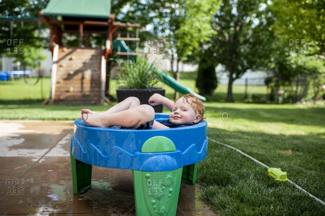 Toddler boy smirking as he lays in water table with clothes on outside