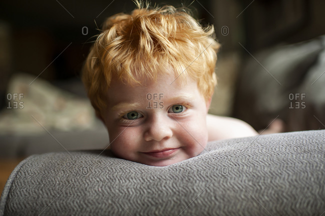 Portrait of toddler boy with red hair laying on couch smiling at home