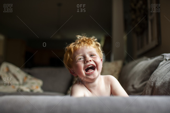 Toddler boy with red hair laughing while laying on couch at home