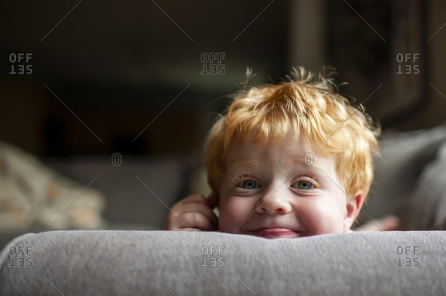 Up close of Toddler boy with silly expression laying on couch at home