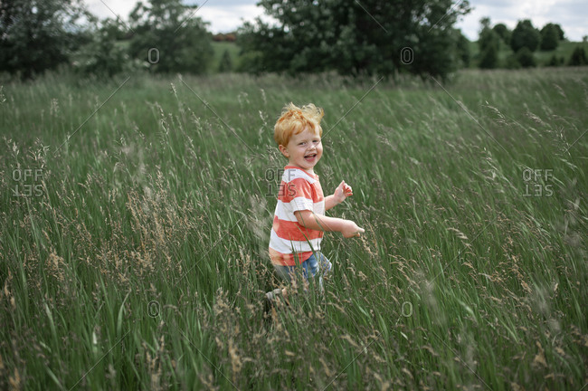 Toddler boy laughing while walking through a long grassy field outside