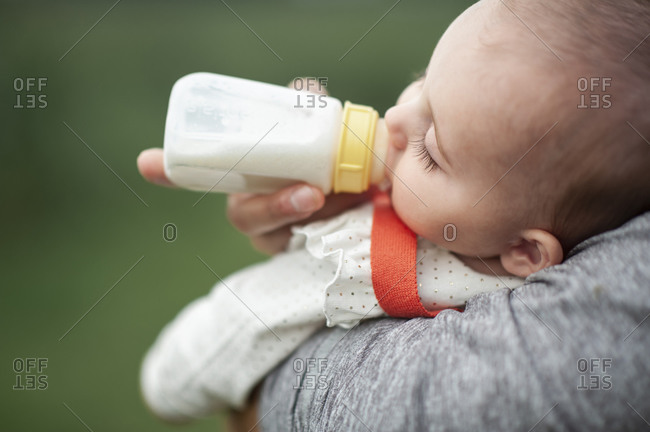 Baby girl sleeping while drinking a bottle outdoors