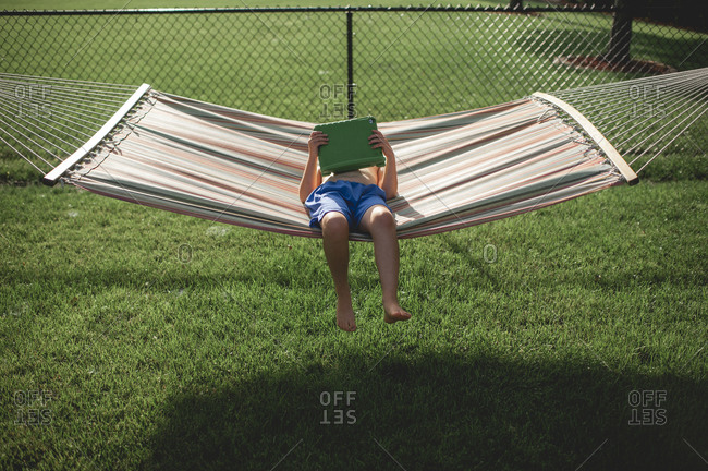 Boy 7-8 years old watching his tablet while laying in hammock outdoors