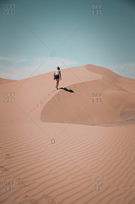 Young Woman hiking on a desert dune leaving footmarks in the sand