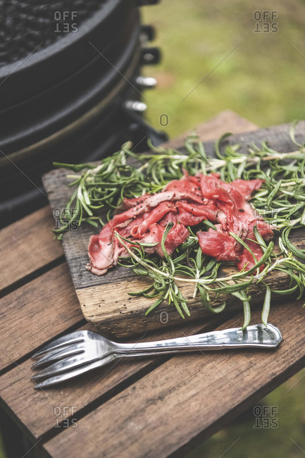 A plate of roast beef with rosemary and a fork