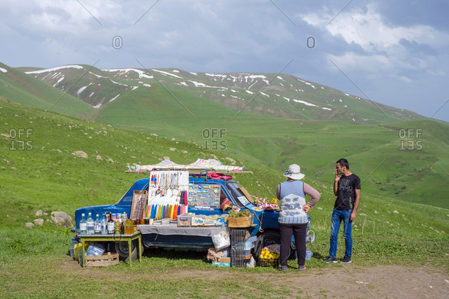 Armenia, Vayots Dzor Province, Aghnjadzor - May 26, 2019: Woman selling souvenirs on a Lada at the Vardenyats Pass (Selim Pass)