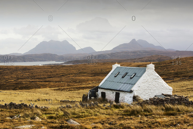 A remote crofting house on Rubha Coigeach in Assynt, North West Highlands, Scotland, UK, looking towards Stac Pollaidh
