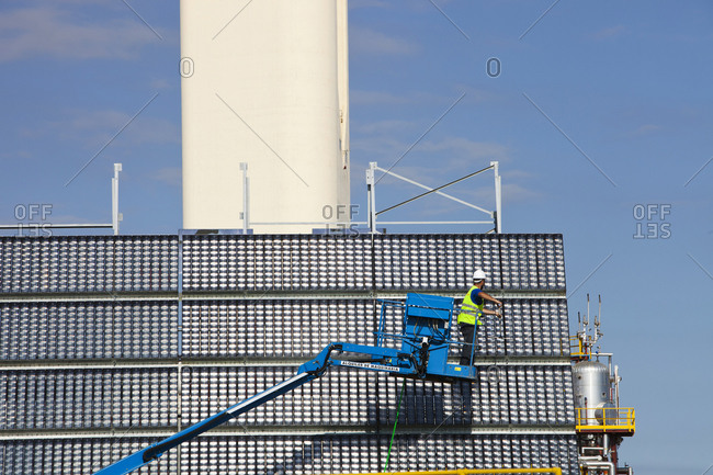 Sanlucar la Mayor, AL, Spain - June 2, 2011: A man cleans high concentration photo voltaic panels