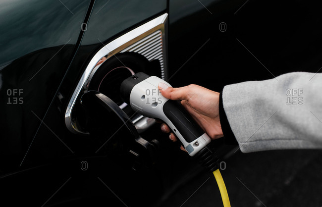 Woman hand and socket plugging in an electric car