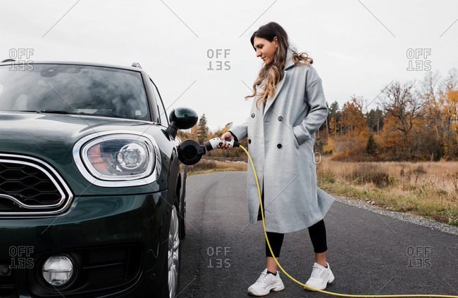 Woman plugging in her electric car on a country road in Sweden