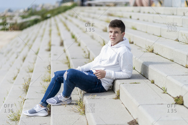 Side view of young man sitting on outdoors staircase, looking away
