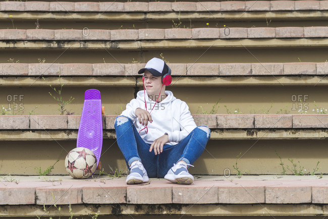 Young teenager male with cap sitting on stairs while listening music