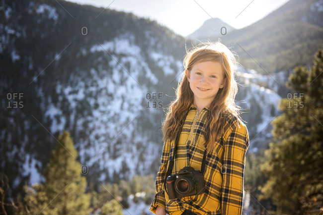 Young Girl With Camera Hiking in the Mountains