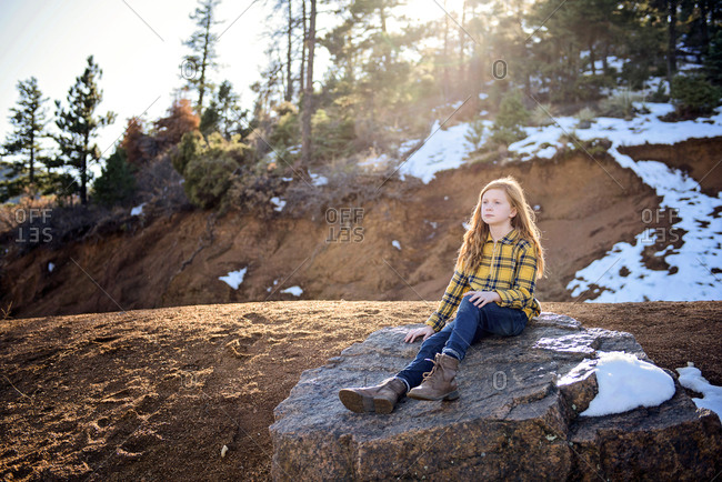 Beautiful Young Girl Sitting on Rock in the Sunshine on Mountain Path