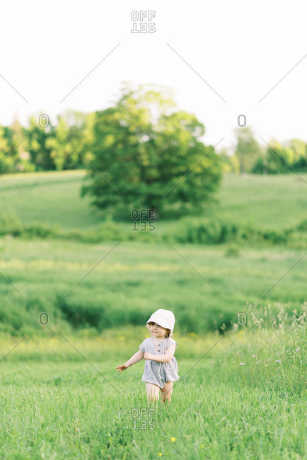 Little girl exploring a meadow.