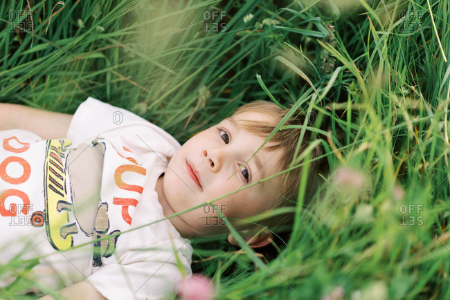 Little boy lying in a meadow.