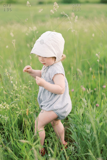 Little girl playing in a grassy meadow.