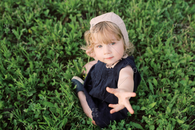 Little girl sitting in the grass.
