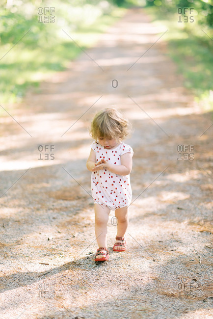 Cute toddler walking a forest path.