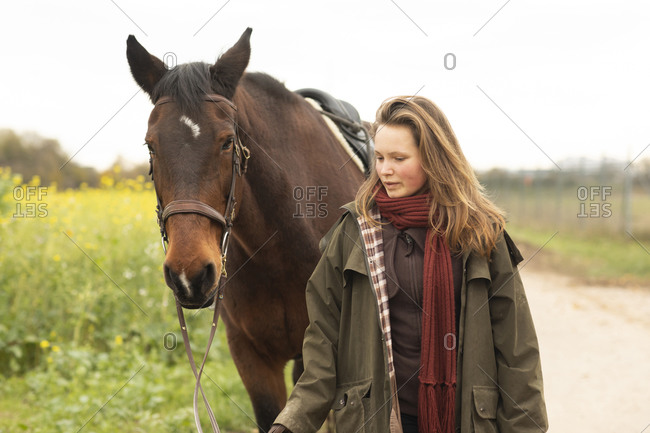 Young woman with a horse on a track