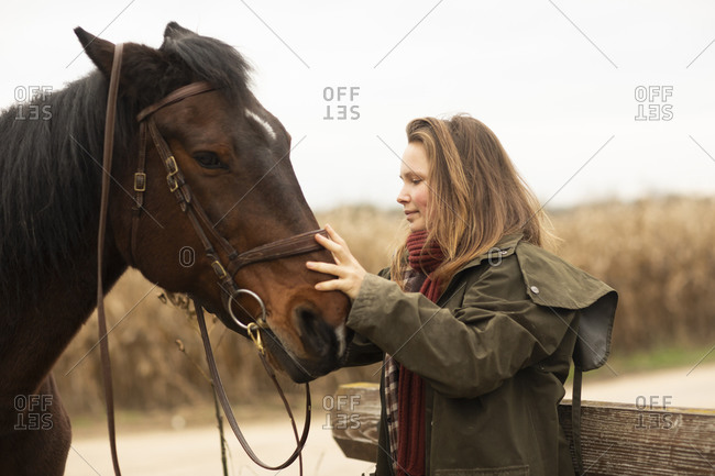 Young horsewoman with a horse outside