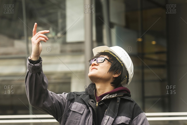 Civil engineer with helmet in front of a building