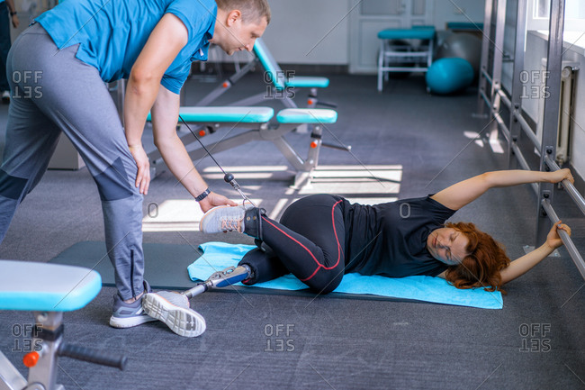 Personal trainer assisting woman with disabilities in her workout